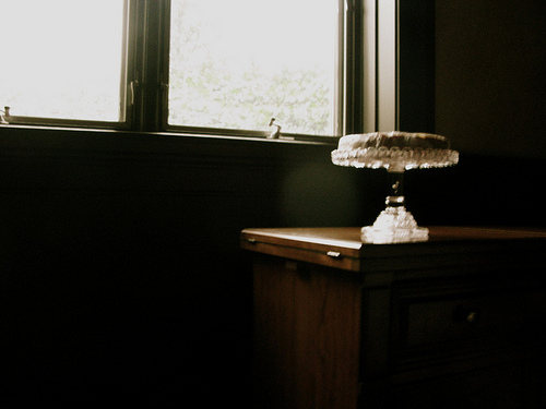 A night lamp on top of a wooden table beside a window.