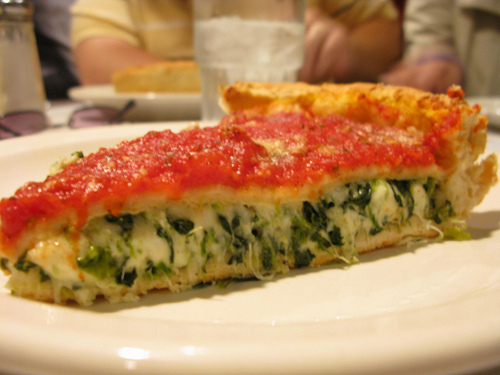 A close up view of a deep dish pizza with yummy filling and super cheesy topping.