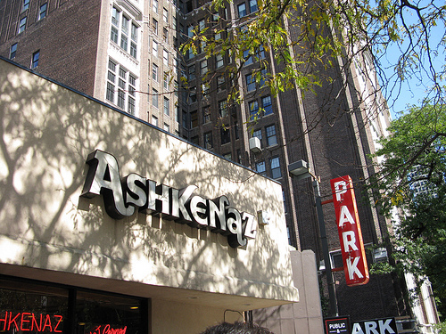 An image of a facade of a building with a signage in front.