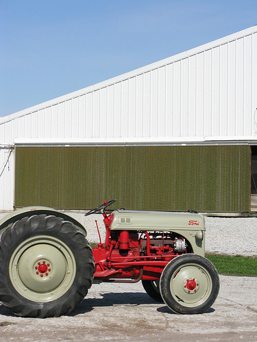An image of a red tractor with a big white shed as the background.