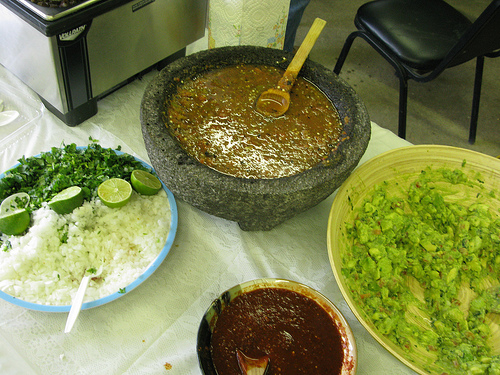 A table filled with various plates and bowls brimming with taco fillings and seasonings.