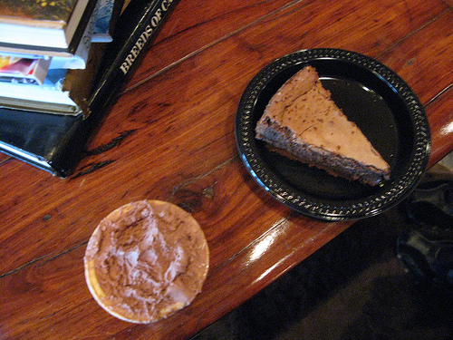 A top view of image of chocolate flourless tart on a black plate and cup of ice cream.