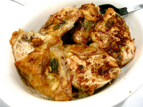 A white plate full of delicious and moist lemony chicken.