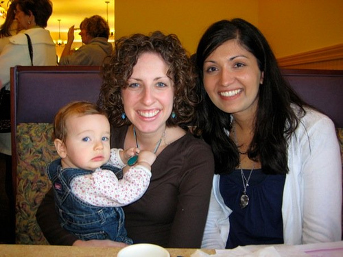 An image of women smiling beautifully and a baby.