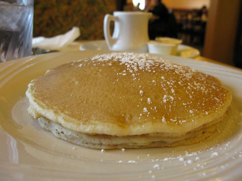 A serving of pancake with a small jar of syrup at the back.