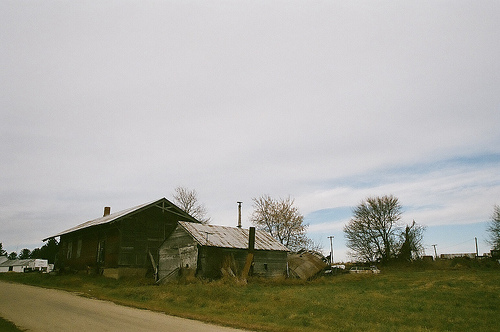 A view of a house along the road with trees at the back.