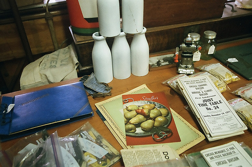 An image of a table with various items on it like bottles , papers, books, and stuff.