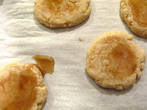 A top view of golden brown cookies on top of a wooden table.