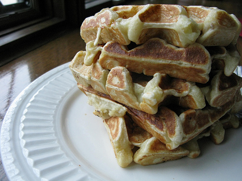 A close up view of waffle stack on a white plate.