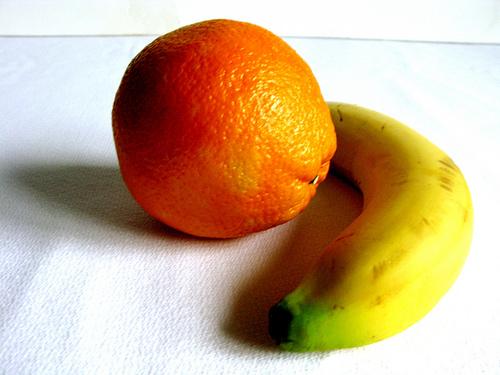 A single orange and banana on a white counter.