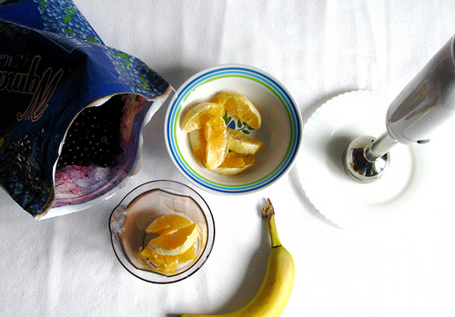 A top view image of blueberries, banana, and orange slices on a white table.