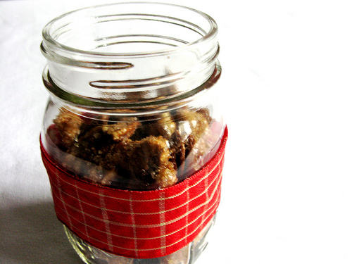 A close up image of candied nuts in a jar against a white background.