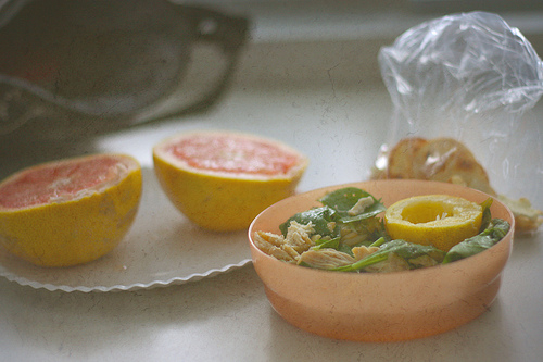 A chicken dish in a small bowl with halved grapefruit at the back.