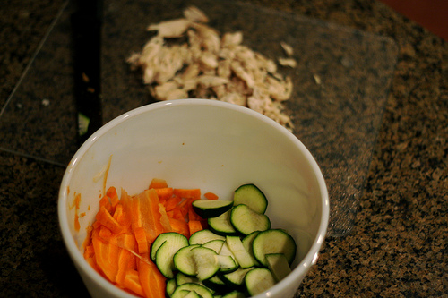 A white bowl filled with carrot and cucumber slices.