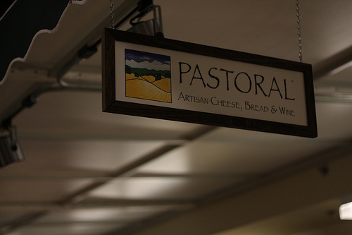 An image of a hanging signage of a store selling artisan cheese, bread, and wine.