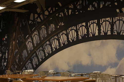 An image of a restaurant setting with a number of tables and chairs with an Eiffel tower theme.