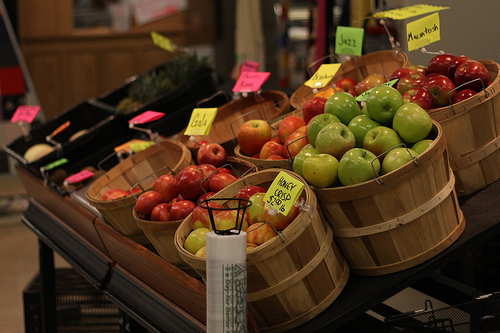 Fresh apples and various produce on display in the market.
