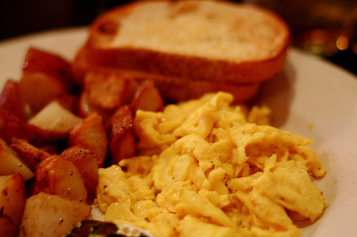 An image of a breakfast meal with scrambled eggs and toast.