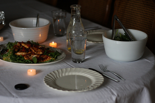 An image of a dining table with candles with plates and complete utensils.