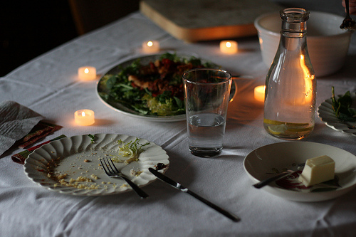 A dining table with candles, a glass, plates, and other dining utensils.