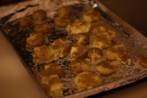 An image of baked baby potatoes in a tray.