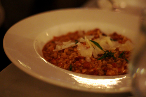 A close up view of a plate of savory creamy risotto with oven-dried tomatoes.