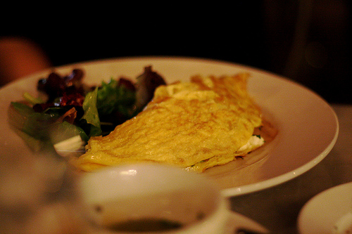 A savory dish of omelet and a salad on a white plate.