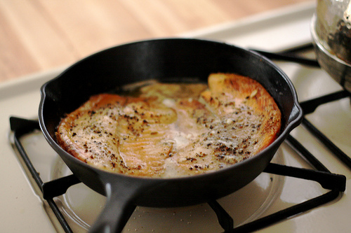 Baked Tilapia fillets in a pan over a stove.