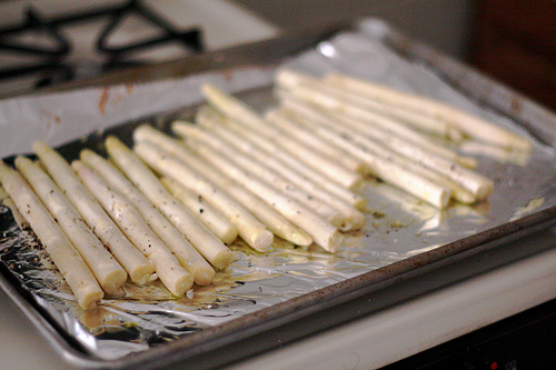 A baking tray lined with foil and full of white asparagus.