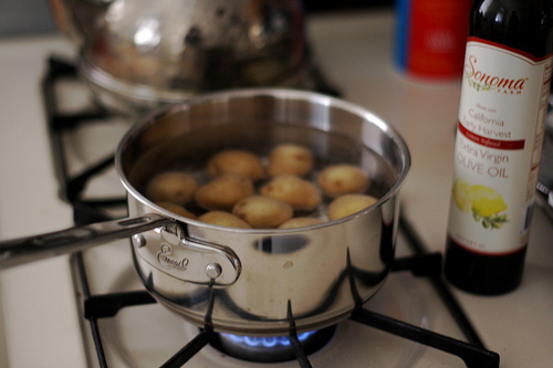 Baby potatoes in a pot filled with water cooking over a stove.