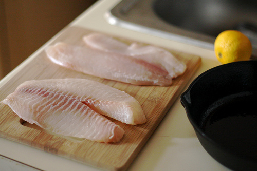 Tilapia fillets on a chopping board.