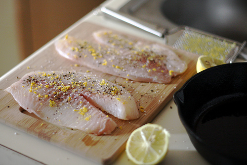 Seasoned tilapia fillets on a wooden chopping board and a sliced lemon on the side.