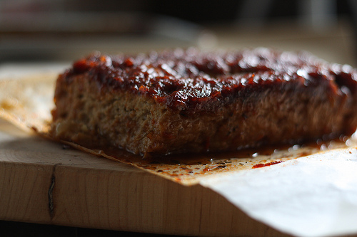 A close up view of a tasty looking meatloaf on a wooden board.