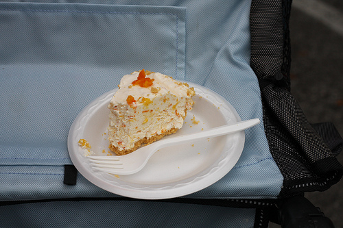 A yummy slice of kumquat pie in styro plate with a plastic fork.