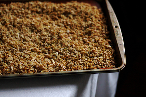 A baking tray filled with homemade granola on top of a table.