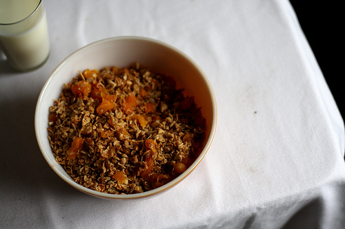 A top view image of a bowl of granola mixture and dried apricots and a glass of milk beside it.