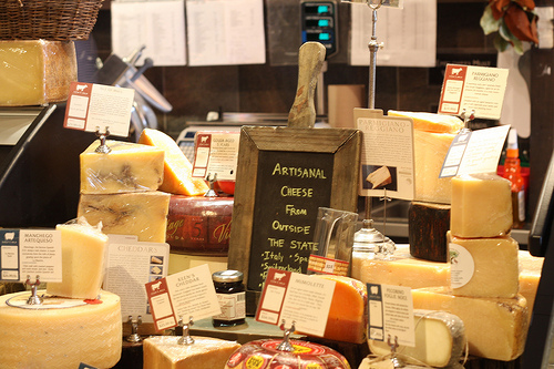 An image of different artisanal cheeses in a cheese / deli shop.