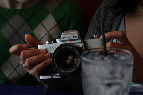 An image of a woman's hand holding a vintage camera.