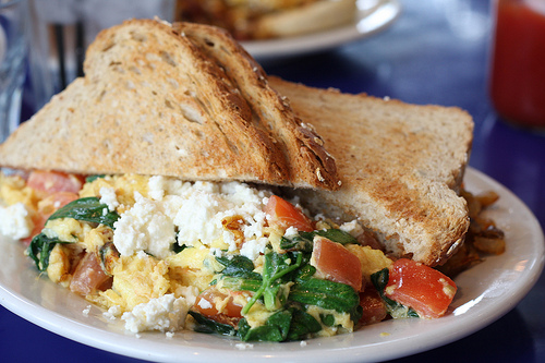 An image of a white plate filled with Popeye scrambler loaded with tomatoes and spinach and feta.