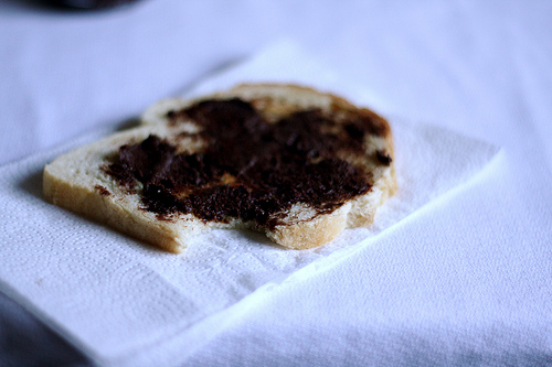 An image of a piece of bread with nutella on a table napkin.