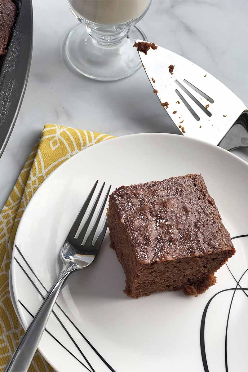 Vertical image of a square of chocolate dessert on a white plate next to a metal fork and a metal serving spatula on a yellow towel.