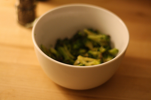 An image showing a bowl on top of a table with pieces of broccoli in it.