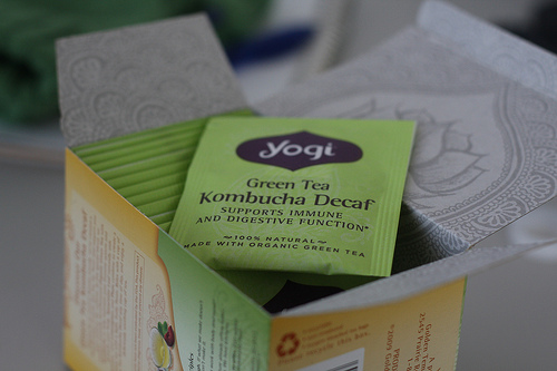 An image showing a box filled small packages of green tea.