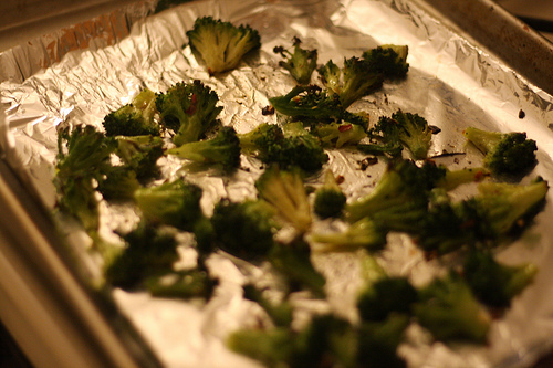 An image showing roasted broccoli on top of am aluminum foil.