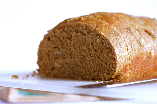 A close up image of a whole grain bread with a knife on the on top of a white chopping board.