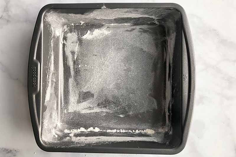 Horizontal overhead image of a greased and floured square metal baking pan.