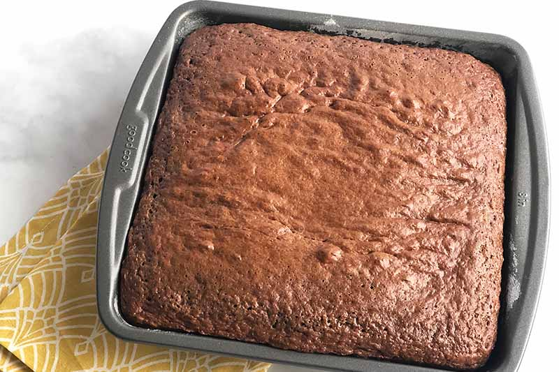 Horizontal image of a baked chocolate cake in a square pan.