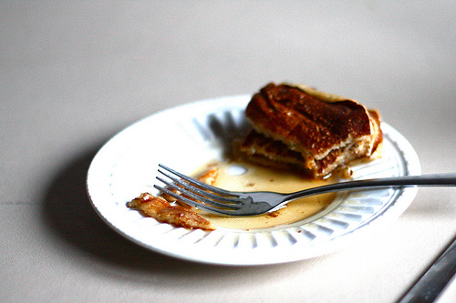 An image of a half-eaten pancake with a fork on a white plate.
