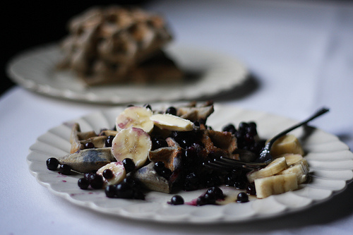 An image of a white plate filled with slices of banana and blueberries with syrup.