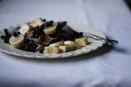 A close up image of buckwheat pancakes topped with blueberries, bananas, and maple syrup.